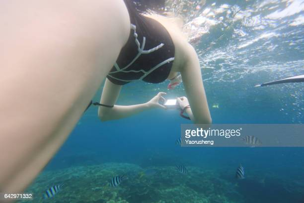 young woman snorkeling with action camera