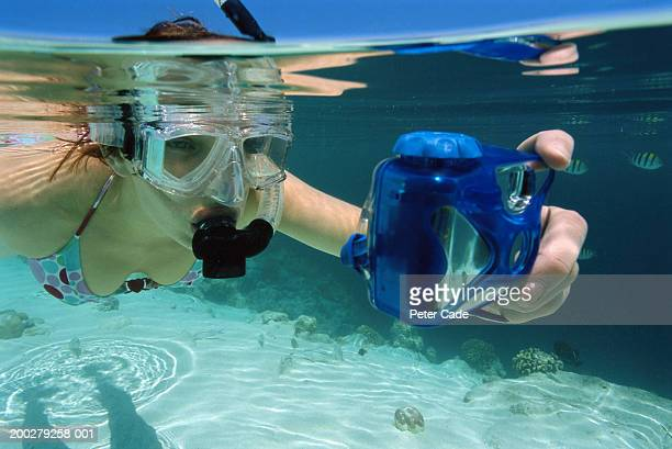 Young woman snorkelling, taking self portrait, underwater view
