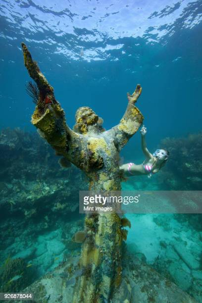 A young woman snorkels near the Christ of the Abyss Statue, Key Largo, Florida Keys. The bronze statue was submerged in the waters of Key Largo, Florida in 1965.