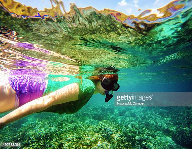 Young woman snorkling in Bali coral reef