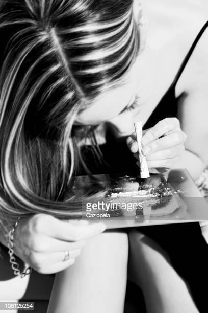giovane donna sniffare droga cocaina su specchio, bianco e nero - sniffare droga foto e immagini stock