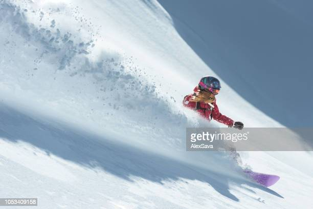 young woman snowboarding in fresh snow - powder snow stock pictures, royalty-free photos & images