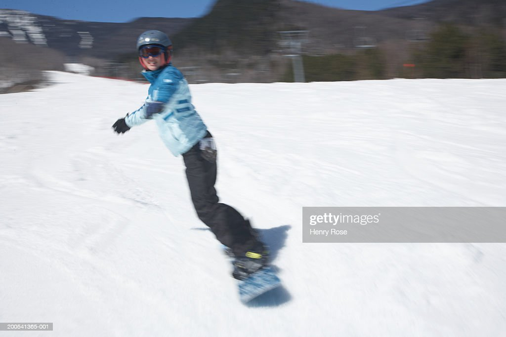 Young woman snowboarding : Stock Photo