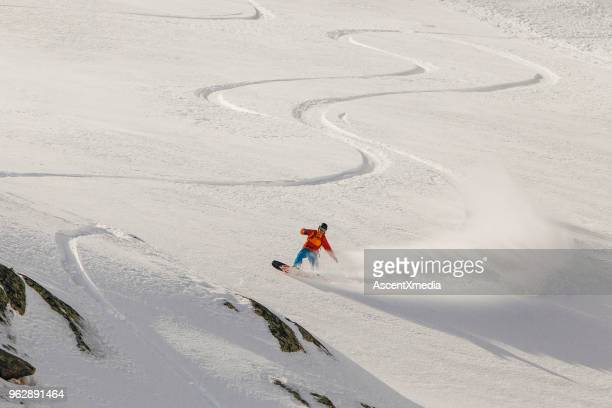 Young woman snowboards through powder snow