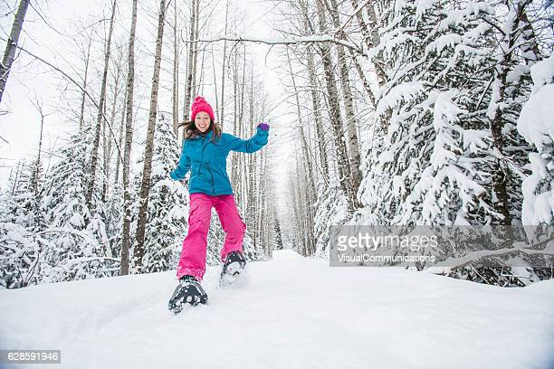 Young woman snowshoeing.