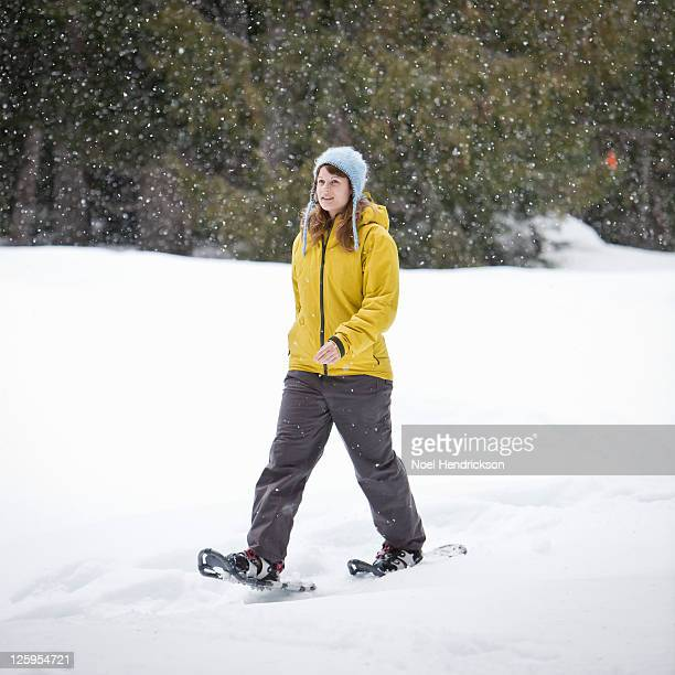 Young woman snowshoes in snowfall