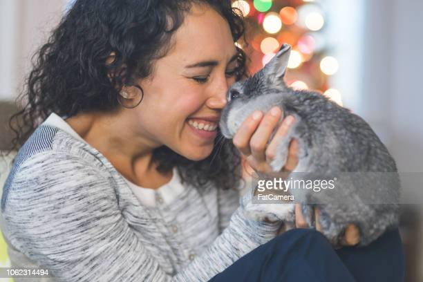 young woman snuggling with her bunny by the christmas tree - affectionate stock pictures, royalty-free photos & images