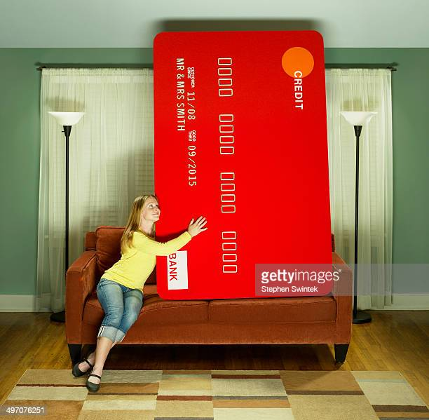 young woman snuggling with oversized credit card - tamanho desproporcionado - fotografias e filmes do acervo