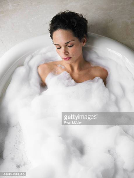 Young woman soaking in bubble bath, eyes closed, elevated view
