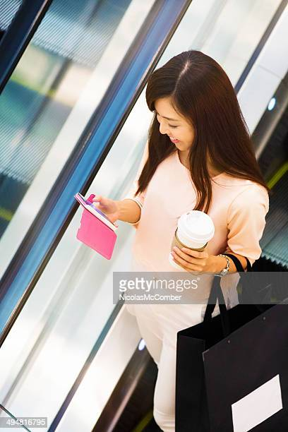 Young woman social networking on escalator