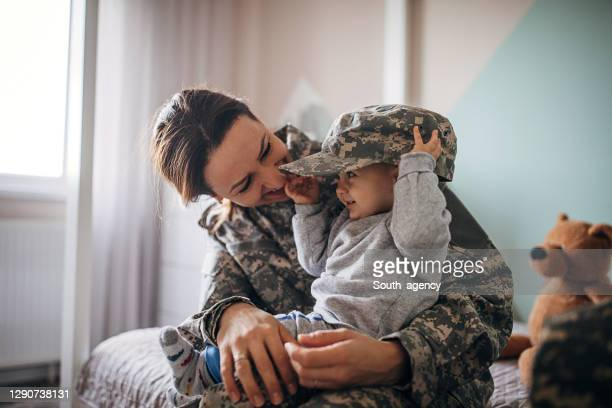 young woman soldier meeting her baby son after a long time - south_agency stock pictures, royalty-free photos & images