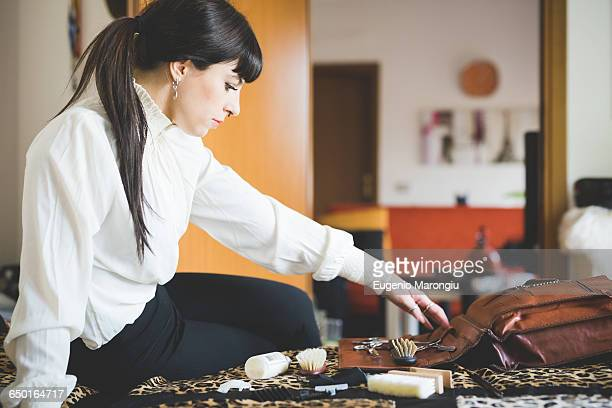 Young woman sorting items on bag in bedroom
