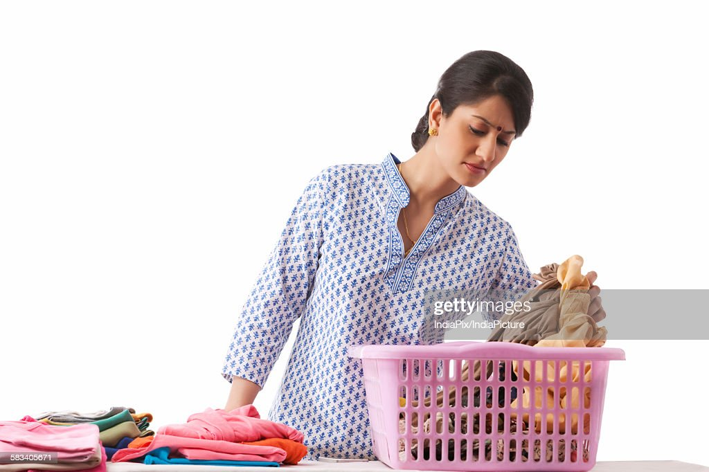 Young woman sorting out clothes : Stock Photo