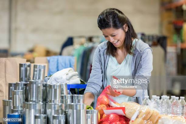 young woman sorts through food in warehouse - food drive stock pictures, royalty-free photos & images
