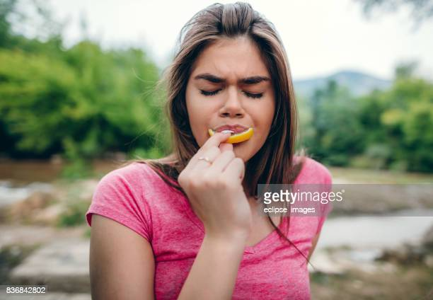 Young woman sour grimace with half of lemon
