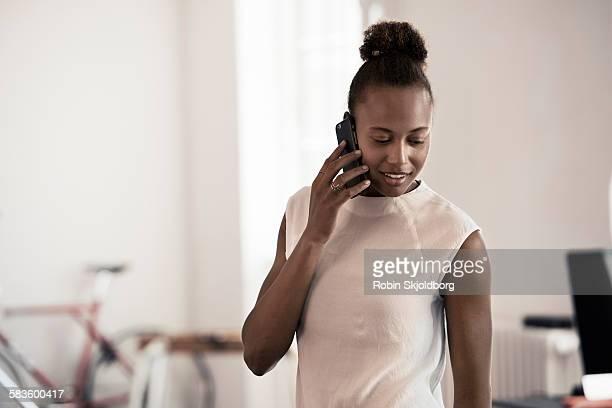 young woman speaking on mobile phone - estilo de peinado de sumo fotografías e imágenes de stock