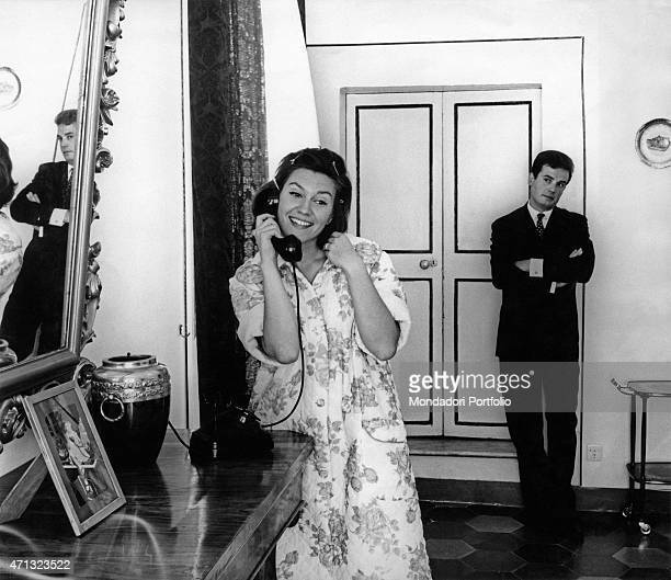 Young woman speaking over the phone while her irritated boyfriend looks at her. Italy, 1960s