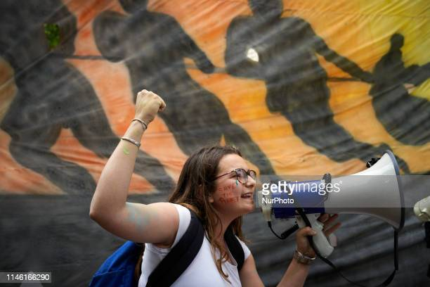 A young woman speaks in a megaphone in front of a painting Following the call of Greta Thunberg for a World School Strike school students and...