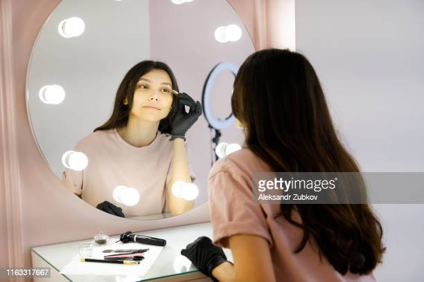 a young woman specialist in gloves plucks eyebrows tweezers in a beauty salon, looking in the mirror. the concept of professional cosmetology, modeling and correction of eyebrow lines, self-care. - aparência - fotografias e filmes do acervo