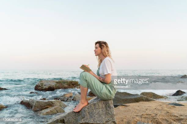young woman spending a day at the seaside, writing in her diary - writer stock pictures, royalty-free photos & images