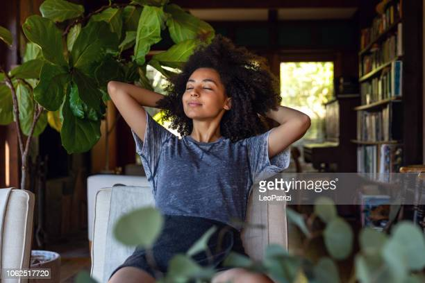 young woman spending a relaxing day in her beautiful home - serene people stock pictures, royalty-free photos & images