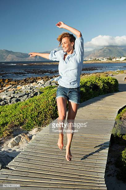 young woman spending summer day on coastline - blue blouse stock pictures, royalty-free photos & images