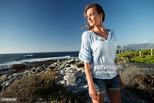 Young woman spending summer day on coastline