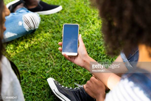 young woman spending time in a park with friends, holding smartphone - black hand holding phone stock pictures, royalty-free photos & images