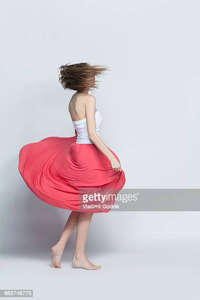 Young woman spinning against white background