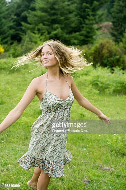 young woman spinning on meadow - sundress stock pictures, royalty-free photos & images
