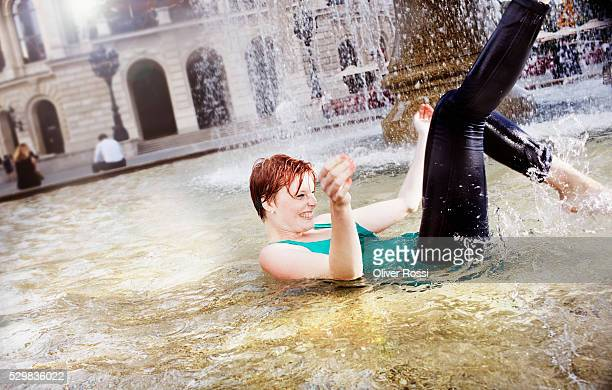 Young woman splashing in water of fountain