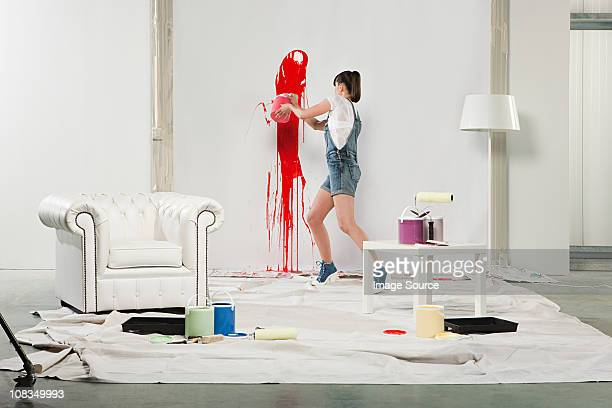 young woman splashing red paint on white wall - throwing stock pictures, royalty-free photos & images