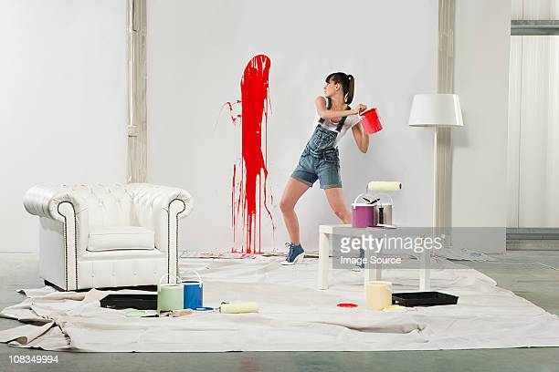 Young woman splashing red paint on white wall