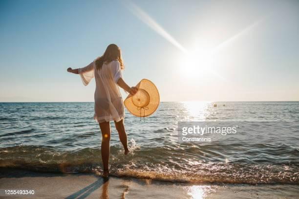 jeune femme éclaboussant l'eau dans la mer peu profonde - vacances à la mer photos et images de collection
