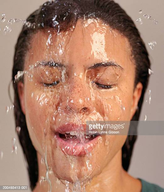 Young woman splashing water on face