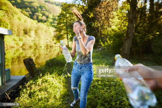 young woman splashing water over her face - women in wet t shirts stock pictures, royalty-free photos & images