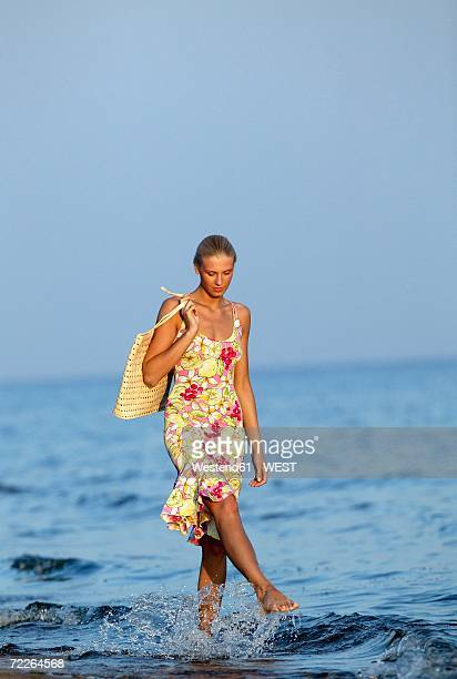 young woman splashing water with foot in sea - woman carrying tote bag stock photos and pictures