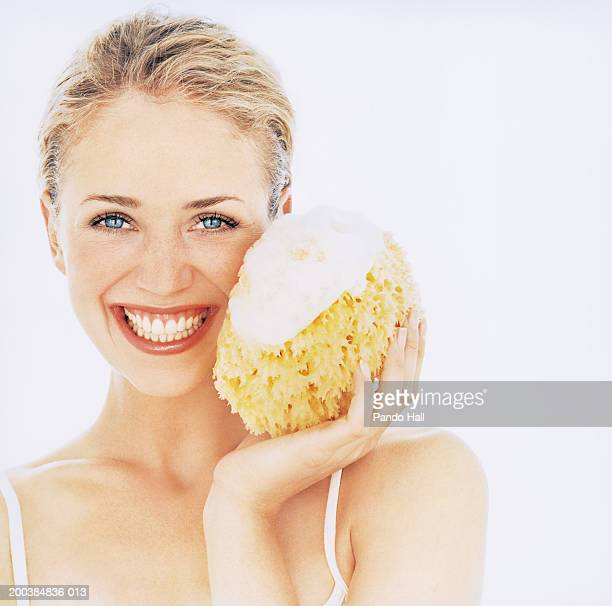 Young woman sponge with suds on, smiling, close up, portrait