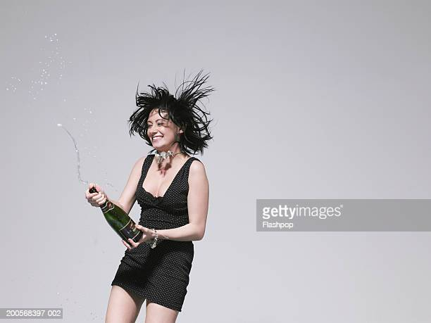 Young woman spraying champagne bottle, smiling