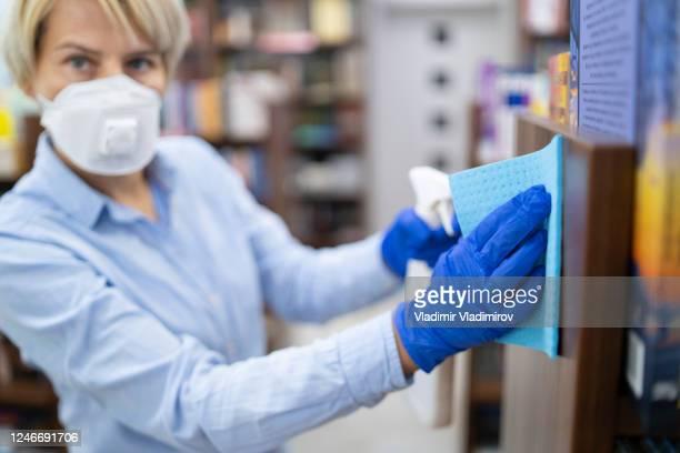 彼女の書店で消毒のための化学物質をスプレー若い女性 - opening event ストックフォトと画像