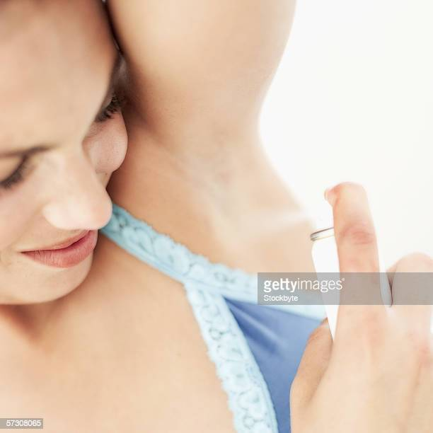 Young woman spraying deodorant on her armpit
