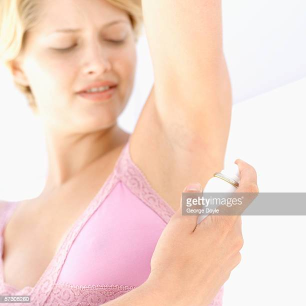 Young woman spraying deodorant to her armpit