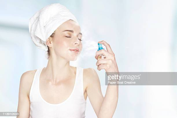 Young woman spraying mist on her face