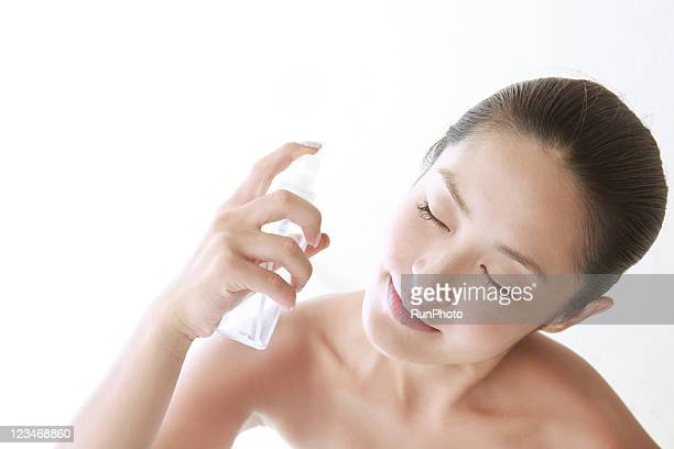 young woman spraying on face for skin care