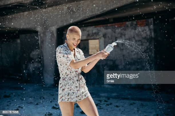 Young woman spraying water from bottle