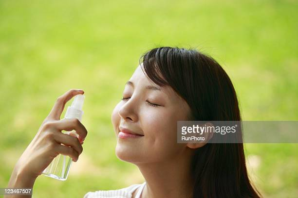 young woman spraying water on face - 目を閉じた ストックフォトと画像