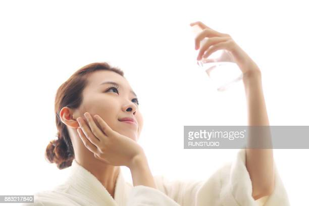 Young woman spraying water on face