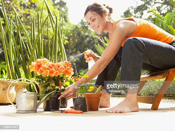 Young woman spraying water on flowers (low angle view)