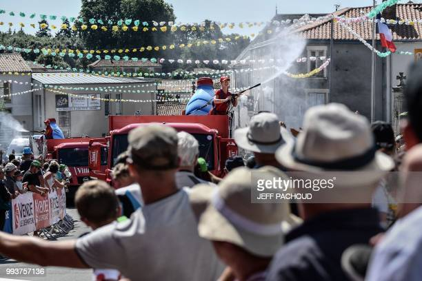 A young woman sprays refreshing water on spectators from a float of the race's publicity caravan prior to the second stage of the 105th edition of...
