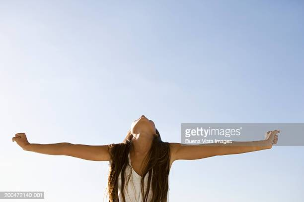 Young woman spreading arms wide, looking upwards